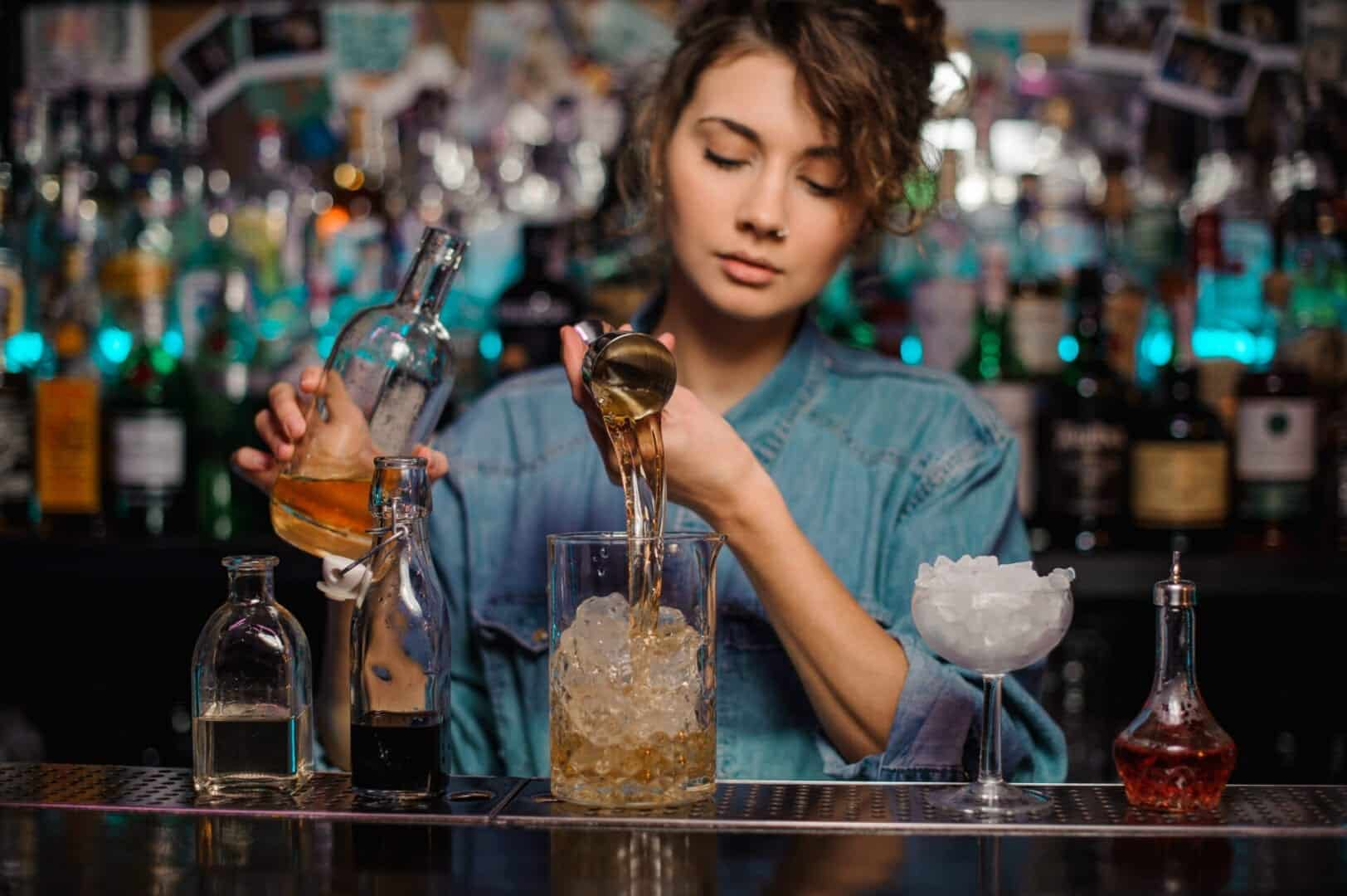 Bartender girl pouring to the measuring glass cup with ice cubes an alcoholic drink from jigger on the bar counter on the blurred background